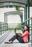 Giovane seduta asiatica dello studente all'aperto, facendo uso di un computer portatile Immagini Stock Libere da Diritti