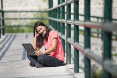 Giovane seduta asiatica dello studente all'aperto, facendo uso di un computer portatile Fotografia Stock