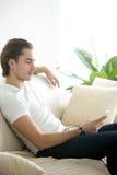 Giovane seduta bella dell'uomo rilassata con il telefono Fotografia Stock Libera da Diritti
