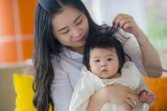 Giovane seduta coreana asiatica sveglia felice della neonata della tenuta della donna alla località di soggiorno di feste che god immagine stock libera da diritti
