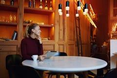 Giovane seduta femminile caucasica felice con la compressa digitale nell'interno di lusso del ristorante dopo il giorno del lavor Fotografia Stock Libera da Diritti