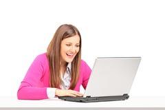 Giovane seduta femminile sorridente ed esaminare un computer portatile Fotografia Stock Libera da Diritti
