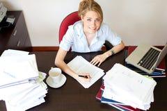 Giovane segretaria che lavora duro su uno scrittorio Immagini Stock
