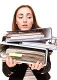 Giovane segretario dentro sollecitato con una tonnellata di documenti Immagine Stock