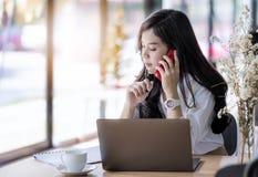 Giovane segretario femminile asiatico che per mezzo dello smartphone Fotografie Stock Libere da Diritti