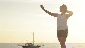 Giovane selfie di presa femminile sul litorale con il fondo leggero del mare stock footage