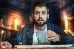Giovane sensibilità barbuta dell'uomo impressionata mentre esaminando lo schermo Fotografie Stock
