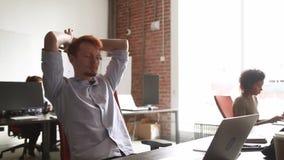 Giovane sensibilità maschio del lavoro del computer di rivestimento degli impiegati soddisfatta con il risultato stock footage