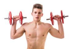 Giovane senza camicia muscolare che esercita le spalle fotografia stock libera da diritti