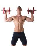 Giovane senza camicia muscolare che esercita le spalle con le teste di legno fotografia stock