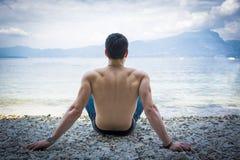 Giovane senza camicia muscolare sul lago in un soleggiato fotografie stock