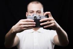 Giovane serio che si fotografa su una macchina fotografica d'annata Fotografia Stock Libera da Diritti