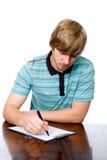 Giovane serio che si siede ad uno scrittorio con una penna a disposizione. Fotografie Stock Libere da Diritti