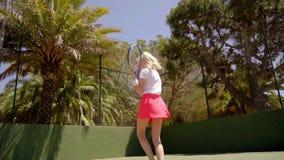 Giovane servizio biondo della donna durante il gioco di tennis video d archivio