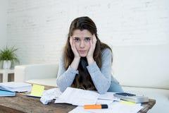 Giovane sforzo preoccupato di sofferenza della donna che fa le fatture domestiche di lavoro di ufficio di contabilità Immagine Stock