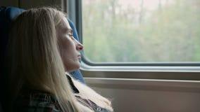 Giovane sguardo caucasico della donna attraverso la finestra mentre viaggiando in treno archivi video