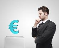 Giovane sguardo dell'uomo d'affari all'euro segno blu sulla a Immagini Stock