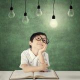 Giovane sguardo dello studente alla lampadina della luce intensa Fotografia Stock