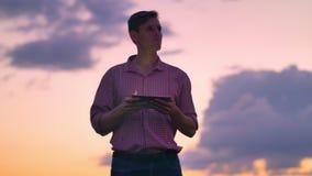 Giovane sicuro bello in camicia che scrive sulla compressa e che guarda in avanti, isolato sul cielo rosa con il fondo di tramont stock footage