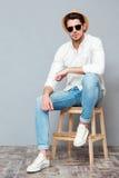 Giovane sicuro in camicia, cappello ed occhiali da sole bianchi Fotografia Stock