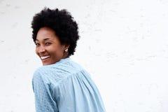 Giovane signora africana sorridente che guarda indietro Fotografia Stock