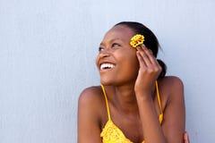 Giovane signora africana sorridente che tiene un fiore Immagine Stock