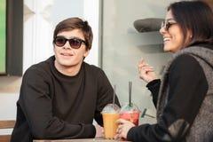 Giovane signora allegra che si siede all'aperto con il suo succo bevente del fratello Fotografia Stock