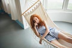 Giovane signora allegra sveglia della testarossa si trova sull'amaca immagini stock