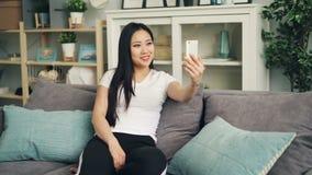 Giovane signora asiatica felice nella fabbricazione della chiamata video online facendo uso dello smartphone moderno a casa che s archivi video