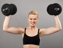 Giovane signora atletica che risolve con i pesi Fotografia Stock Libera da Diritti