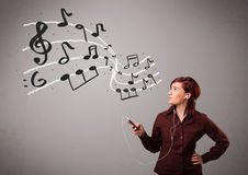 Giovane signora attraente che canta e che ascolta la musica con il musica Fotografie Stock Libere da Diritti