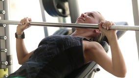 Giovane signora attraente che risolve nella palestra - bilanciere di sollevamento - petto muscles l'esercizio archivi video