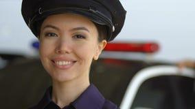 Giovane signora attraente della pattuglia che sorride alla macchina fotografica, ufficiali di polizia professionisti archivi video
