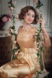Giovane signora attraente sulle oscillazioni fiorite verticale immagini stock