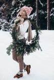 Giovane signora bionda con la corona di natale nella foresta di inverno Immagine Stock Libera da Diritti