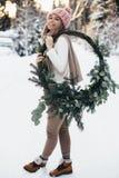 Giovane signora bionda con la corona di natale nella foresta di inverno Fotografia Stock