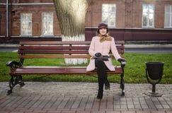 Giovane signora in cappotto dentellare su un banco Fotografia Stock Libera da Diritti