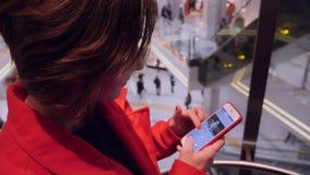 Giovane signora caucasica attraente di affari in cappotto rosso facendo uso del suo telefono in un elevatore archivi video