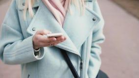 Giovane signora caucasica del movimento lento che per mezzo dello smartphone Bionda graziosa 20s con capelli biondi lunghi che fa stock footage
