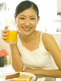 Giovane signora che beve il suo succo di arancia fotografie stock libere da diritti