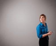 Giovane signora che canta e che ascolta la musica con lo spazio della copia Fotografie Stock