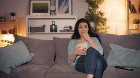 Giovane signora che guarda TV e che mangia popcorn a casa che si siede sullo strato da solo stock footage
