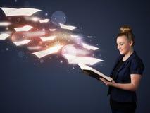 Giovane signora che legge un libro con gli strati di volo che escono dalla b Fotografie Stock