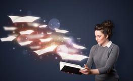 Giovane signora che legge un libro con gli strati di volo che escono dalla b Fotografie Stock Libere da Diritti