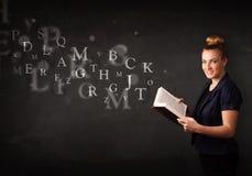 Giovane signora che legge un libro con le lettere di alfabeto Fotografia Stock Libera da Diritti