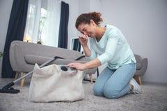 Giovane signora che pulisce tappeto polveroso che soffre dall'allergia della polvere Fotografie Stock