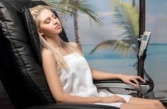 Giovane signora che si rilassa nella sedia di massaggio Immagine Stock Libera da Diritti
