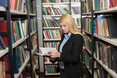Giovane signora che sta fra gli scaffali di libro nello sguardo delle biblioteche Fotografie Stock Libere da Diritti