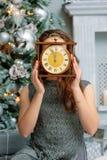 Giovane signora che tiene gli orologi dietro il fronte vicino all'albero di Natale immagine stock libera da diritti