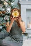 Giovane signora che tiene gli orologi dietro il fronte vicino all'albero di Natale fotografia stock libera da diritti